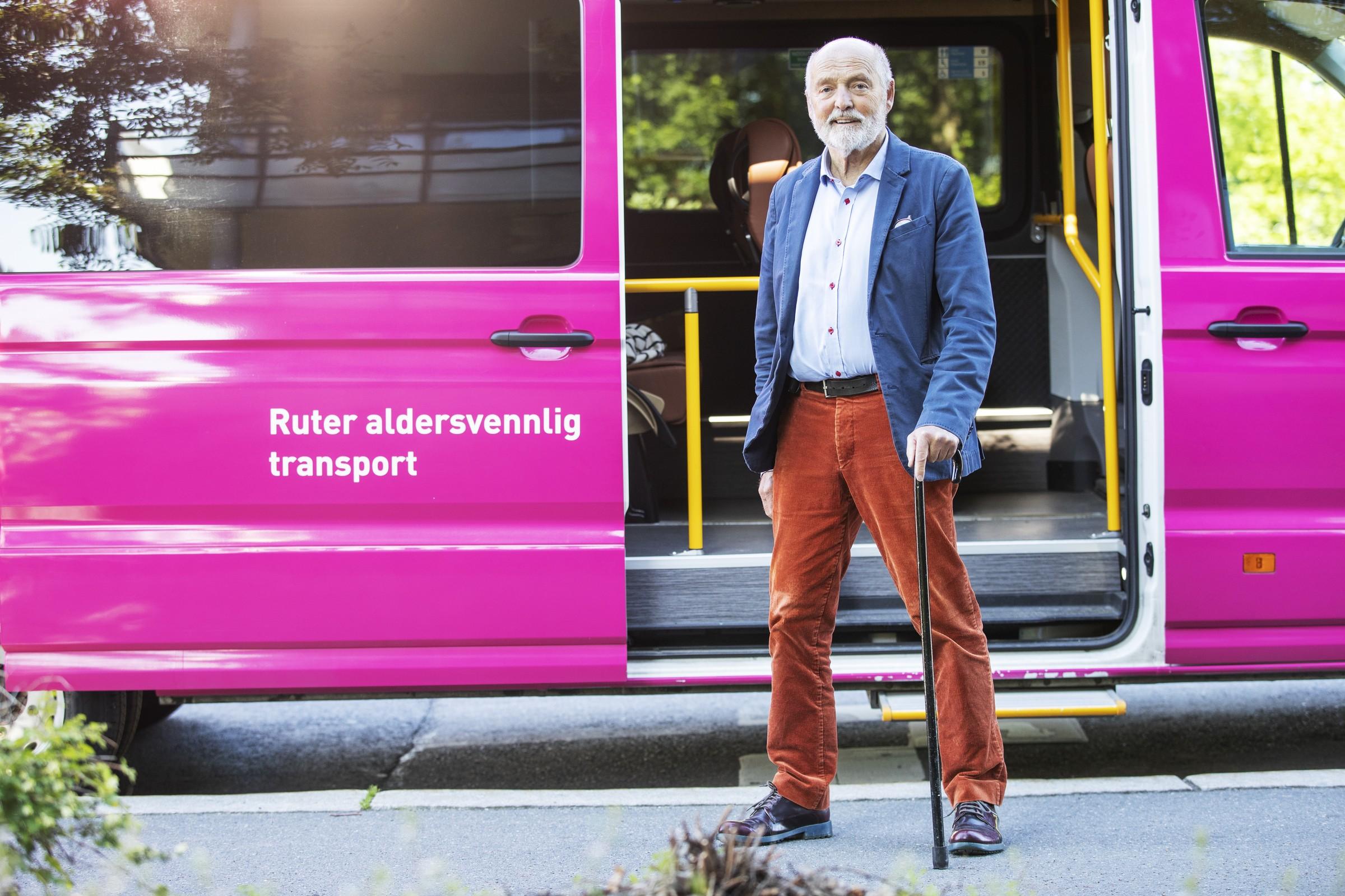 Foto av mann med stokk utenfor en rosa buss; Aldersvennelig transport