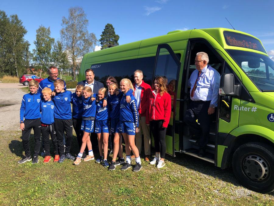 En gjeng barn i idrettstøy som står foran en Ruter buss.