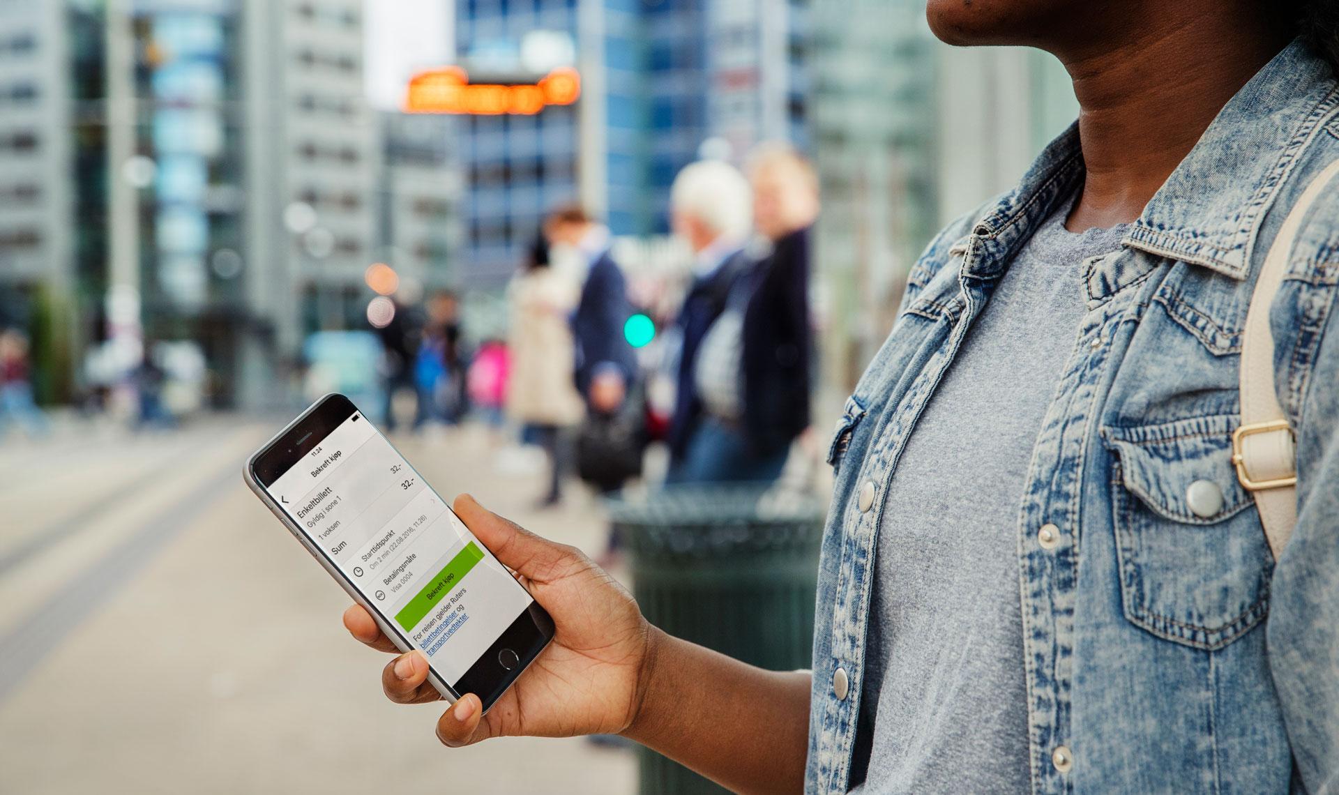Bilde av jente som holder en mobil som viser appen Ruter billett