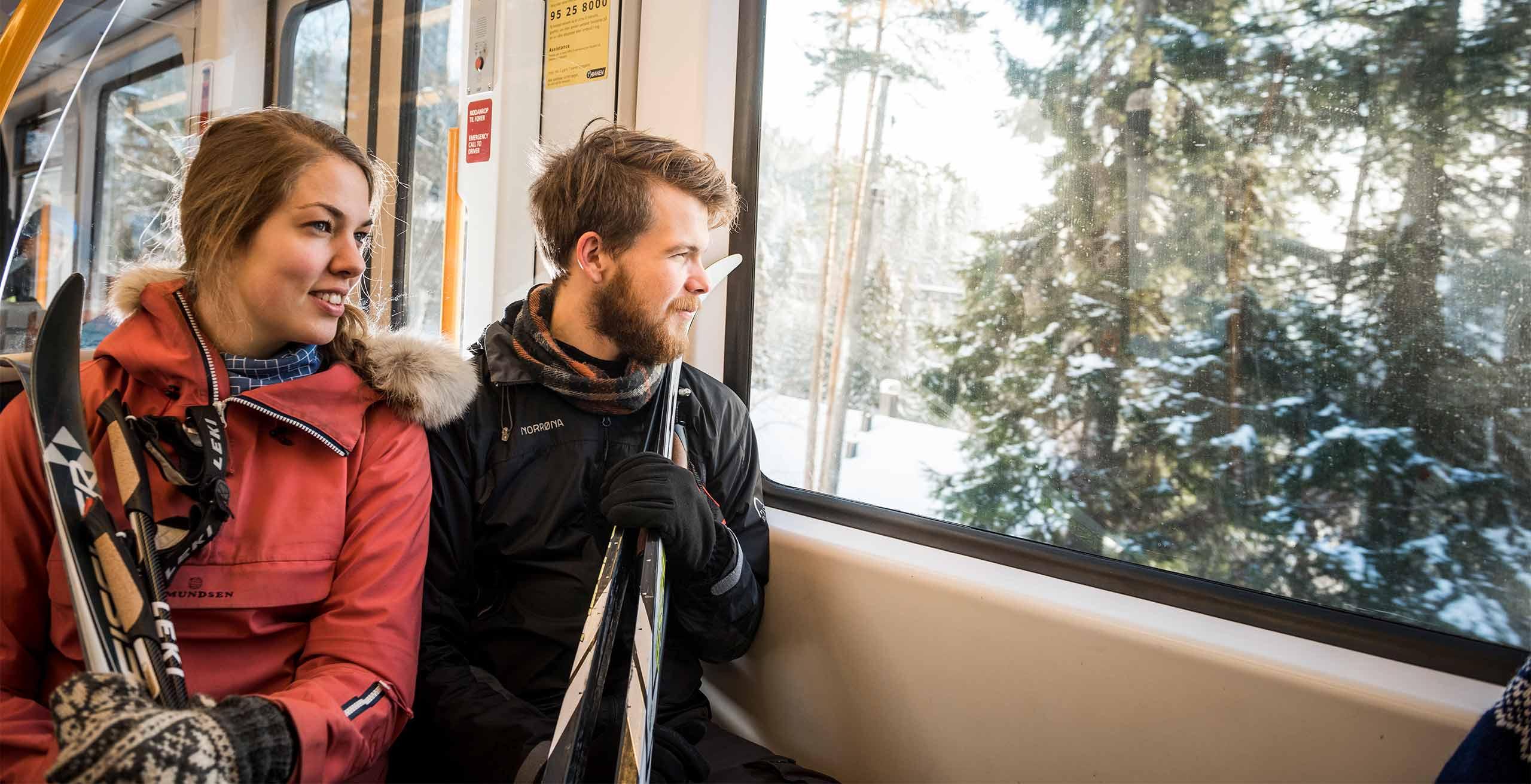 Bilde av to passasjerer med langrennski på t-banen