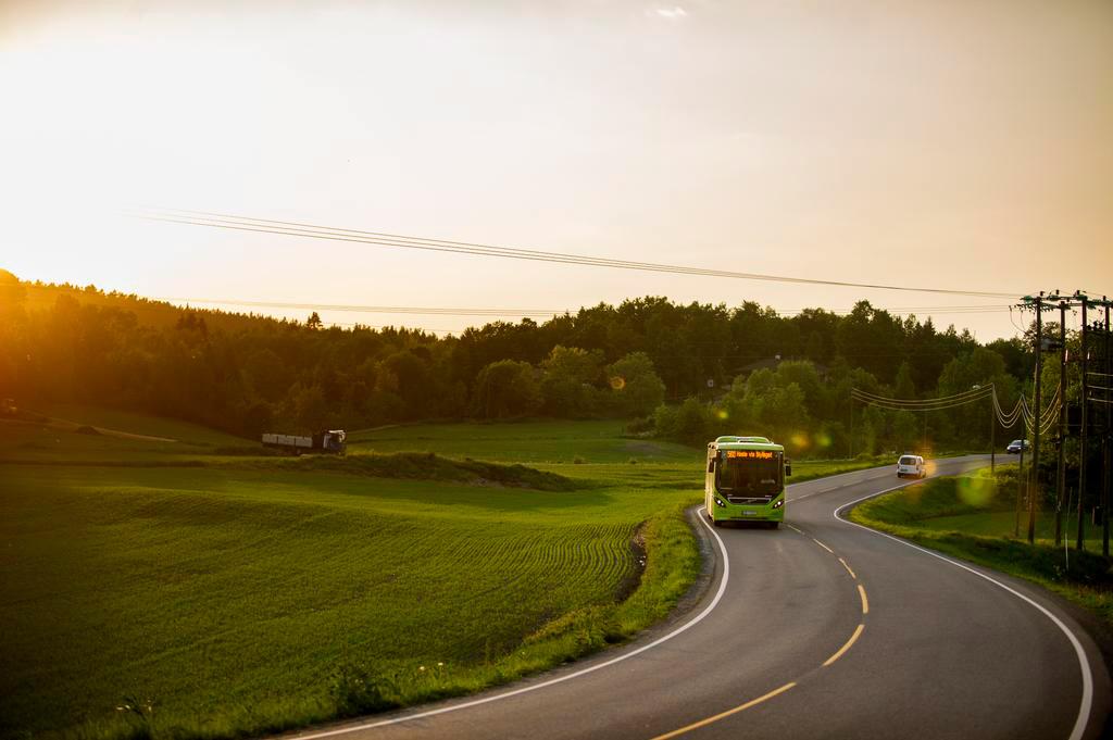 Region buss som kjører langs en rolig vei i solnedgangen.