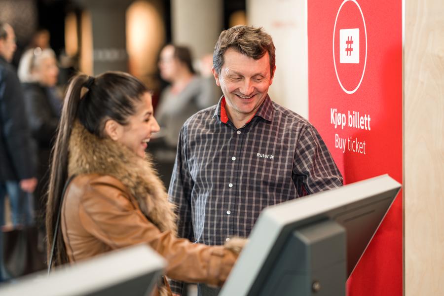 Ruter-ansatte som hjelper en kunde med å kjøpe billett på automat.