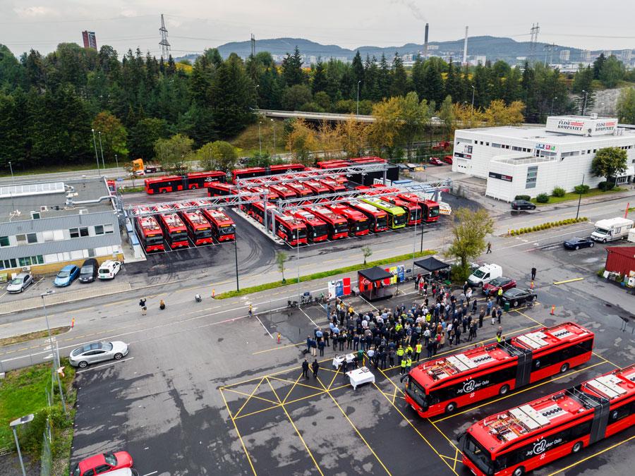 Foto i fugleperspektiv over en parkeringsplass full av røde busser.